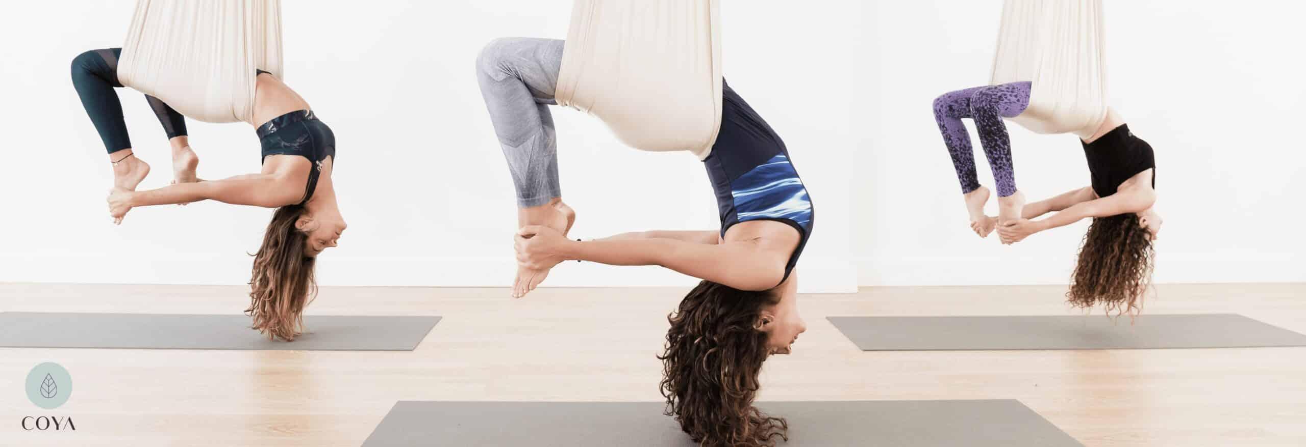 Τρεις γυναίκες ασκούν Aerial Yoga